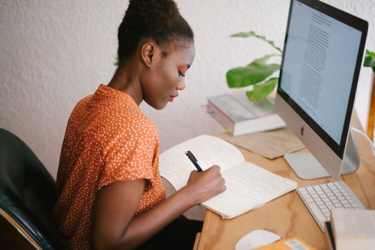A black woman writing ways to make money as a freelance writer