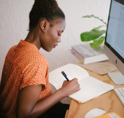 A black woman writing ways to make money as a freelance writer