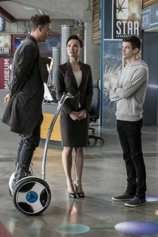 """The Flash -- """"Borrowing Problems from the Future"""" -- Image FLA310b_0077b.jpg -- Pictured (L-R): Tom Cavanagh as Harrison Wells, Lindsay Maxwell as Olga and Grant Gustin as Barry Allen -- Photo: Katie Yu/The CW -- © 2016 The CW Network, LLC. All rights reserved."""