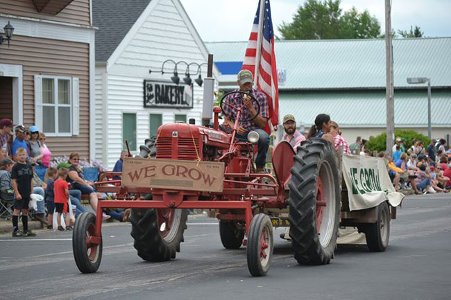 Farmer Eric representing We Grow LLC on the Farmall Super C in the Rib Lake Ice Age Days Parade