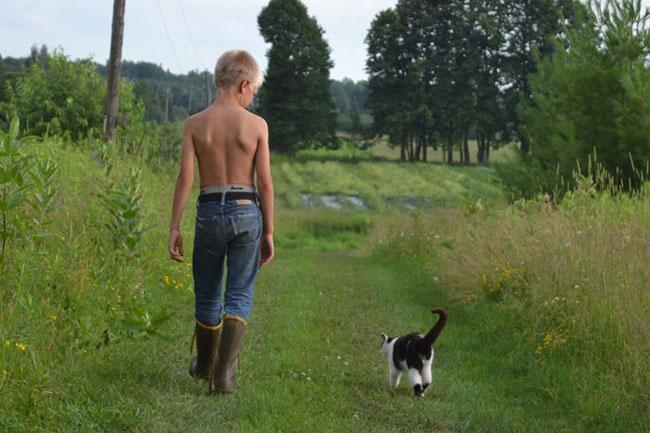 Farmer Gus and cat Dan walking to the field at We Grow LLC