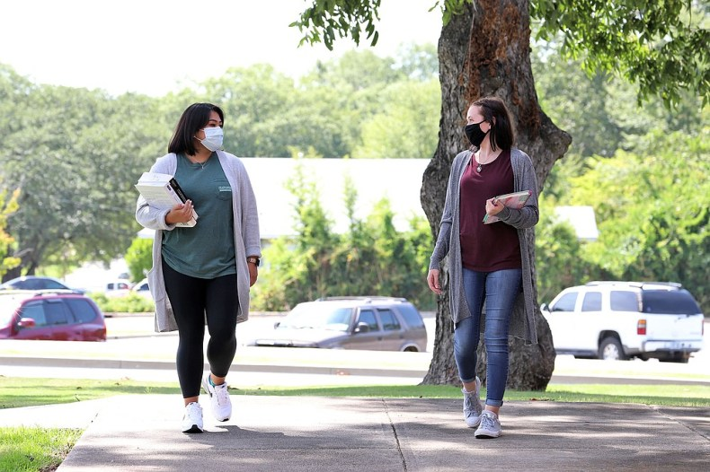 South Arkansas Community College students Amy Lee, left, and Savanna Morgan, both in protective masks, walk on the college's West Campus on Monday, the first day of the fall semester at SouthArk. (Contributed)