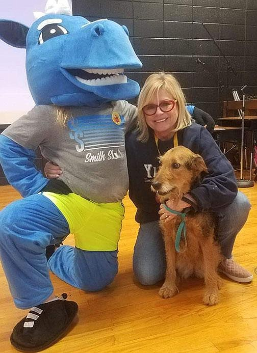 """Former Springdale Elementary teacher Kathy Short poses March 13 with the school's mascot and her dog. Short decided to retire this summer after 37 years in education because she didn't feel comfortable going back to school during a pandemic. """"It's not my age. I'm healthy. I just didn't feel safe,"""" she said. """"I didn't want to retire like this."""" (Special to the Democrat-Gazette)"""