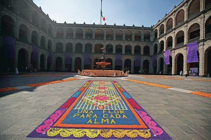 """A patio inside the presidential palace is decorated with the traditional colors of Day of The Dead, with the Spanish message """"A flower for each soul,"""" in Mexico City, Saturday, Oct. 31, 2020. The holiday isn't the same in a year so marked by death in a country where more than 90,000 people have died of COVID-19, many cremated rather than buried and with cemeteries forced to close. (AP Photo/Fernando Llano)"""