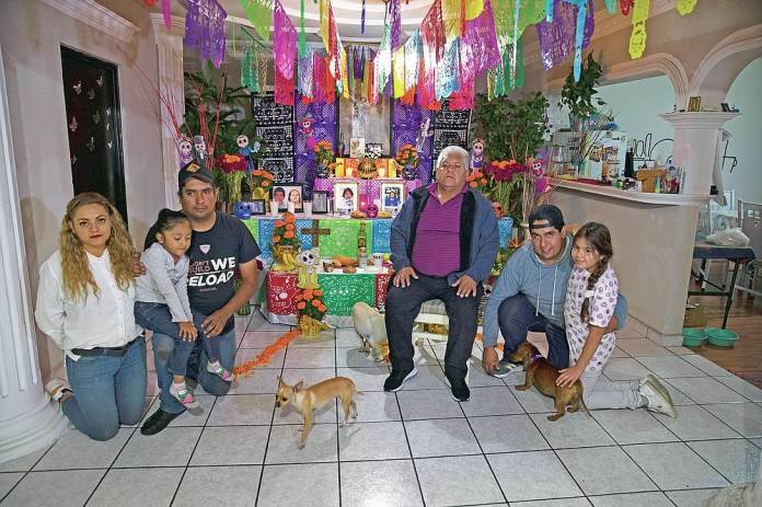 """Salvador Cervantes Torres, center, a recovered COVID-19 patient, and his family pose for photos on a Day of the Dead altar for his wife Ivone Guadalupe Lozano Garcia and his mother in law Silvina Garcia, who died of complications related to coronavirus, at their home in Ecatepec, Mexico, Saturday, Oct. 31, 2020. Mexican families traditionally flock to local cemeteries to honor family members who died as part of the """"Day of the Dead"""" holiday, every Nov. 1 and 2, but according to authorities cemeteries will be closed this year to help slow the spread of COVID-19. (AP Photo/Marco Ugarte)"""
