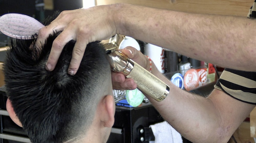 A Spa City Barbershop employee cuts a customer's hair.  - Photo by Tyler Wann from The Sentinel Record
