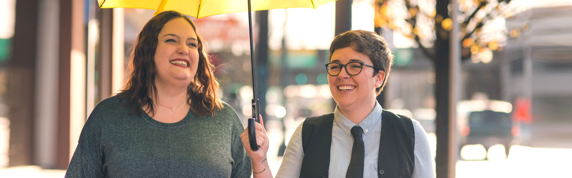 women smiling under yellow umbrella