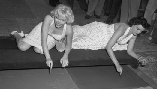 Marilyn Monroe and Jane Russell signing their names on the walk of fame at Grauman's Chinese Theatre