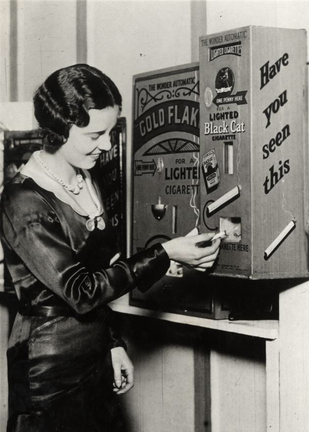 Cigarette machine delivering lit cigarettes, 1930s