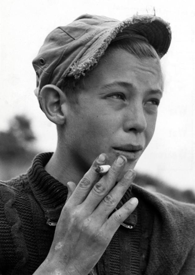 Smoking boy in a playground, 1950s