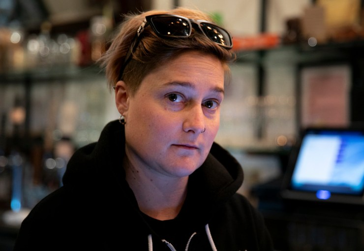 "Bartender Liz McAlpine, 31, worries about paying rent and her student loans after taking a massive reduction in hours at her restaurant job in Oakland following the shelter in place mandate in Alemeda and surrounding counties earlier this week. ""I don't know what any of us are going to do,"" she said. Photo by Anne Wernikoff for CalMatters"