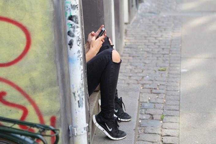 Mädchenbeine am Gehsteig mit Handy