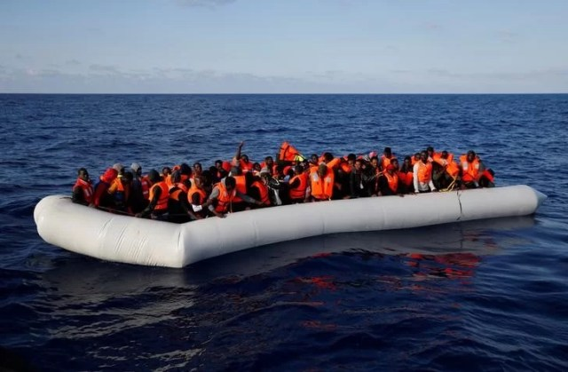 Migrants in a dinghy await rescue by the Migrant Offshore Aid Station (MOAS) around 20 nautical miles off the coast of Libya, June 23, 2016. REUTERS/Darrin Zammit Lupi