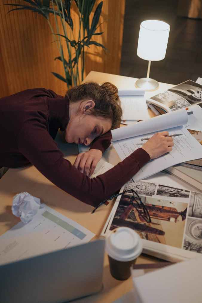 A woman exhausted fell asleep on her desk while working