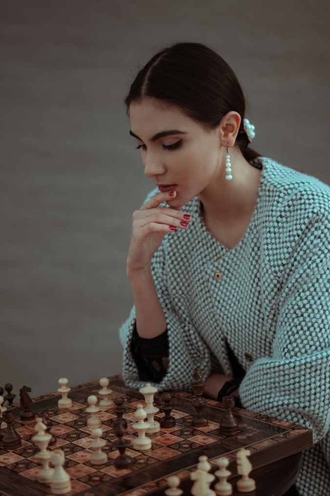 A woman is thinking her next chess move