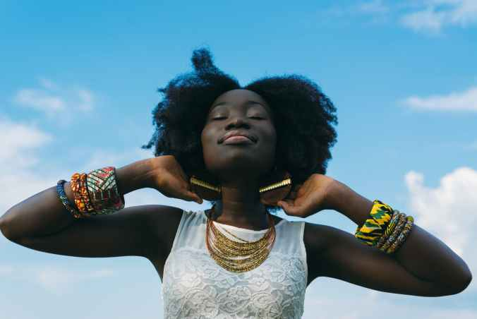 black woman with her eyes closed is smiling in joy
