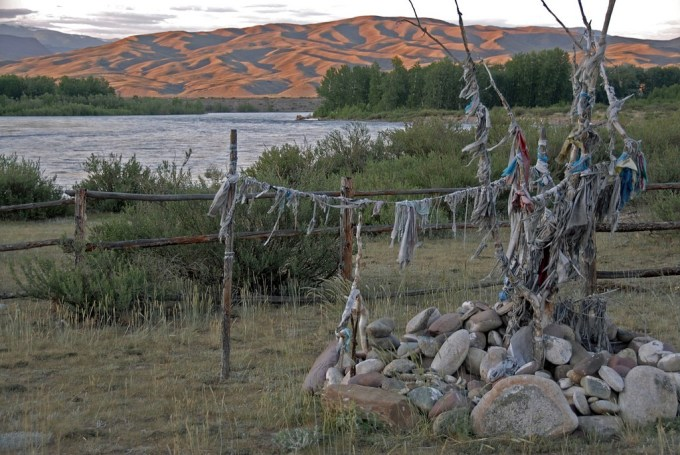 Ovoo --a type of shamanistic cairn found in Mongolia or nearby areas--like here in Tuva. They are religious sites often used in giving thanks to the earth--notably mountains and sky, as well as used in various Buddhist ceremonies. Travelers leave rocks, sacred ribbons with religious sayings, flowers or anything sacred to them, as they pass by and add their own prayer. Photo by  cjuel/Flickr