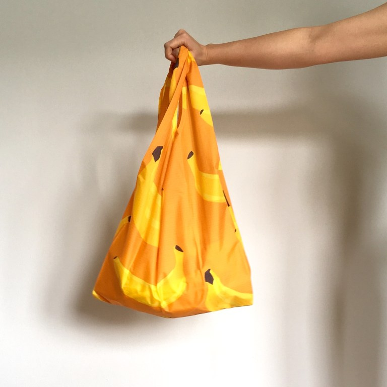 Standard Baggu in banana print, shown held in a hand.