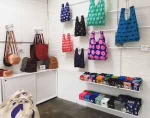 Interior of the Baggu store in Oakland. Bags are displayed on the walls, and on hooks.