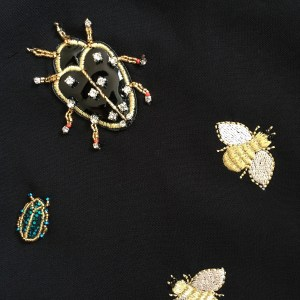 Closeup of the Victoria Beckham for Target embellished bug dress, which has beetles and bees and other bugs on it. The bugs are beaded or embroidered.