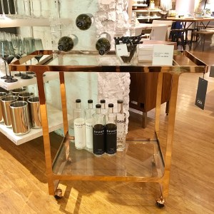 CB2 Dolce Vita bar cart, shown in the store. The shelves are glass and the metal is bright gold.