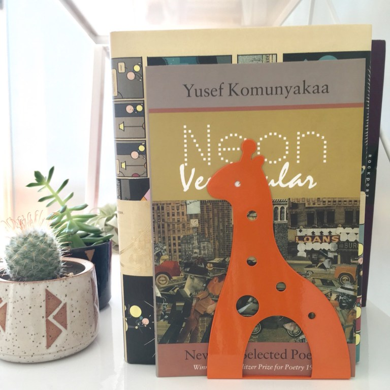 Daiso giraffe bookend holding up books. The book at the end is Neon Vernacular by Yusef Komunyakaa