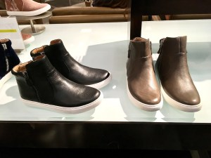Two pairs of high top sneakers by Gentle Souls, in black, and in brown.