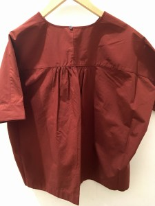 Back of a Uniqlo cotton blouse in a red-orange color.