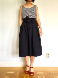 Uniqlo high waist midi flare skirt, as modeled by me. The skirt is navy and paired with a striped tank top and red sandals.