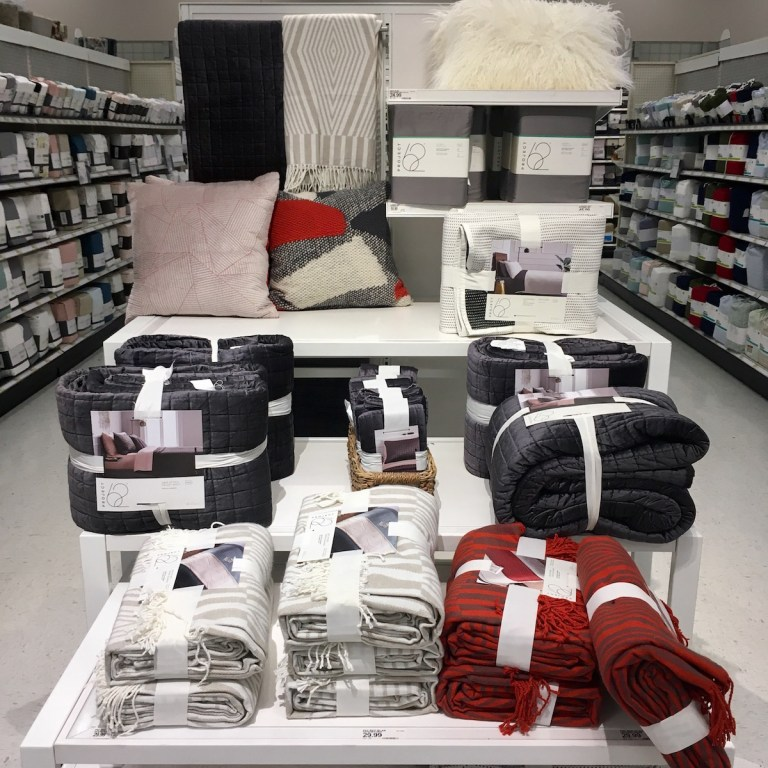 A display of quilts, throws, bedsheets, and throw pillow in a Target store.