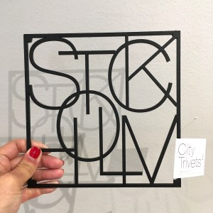 A metal trivet made up of letters, which spell out Stockholm. The trivet is square shaped and the letters overlap one another.