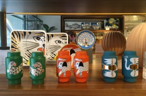 A row of six vases on a shelf at Svensky Tenn. Two have a large cat, perhaps a leopard, two have elephants, two have birds. The vases are colorful.