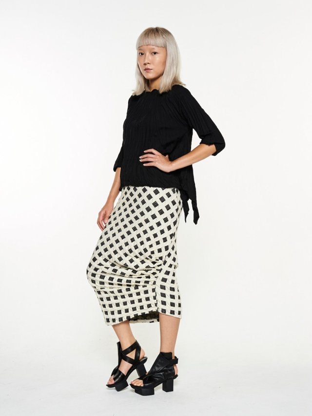 Model wearing a black top and long black and white skirt.