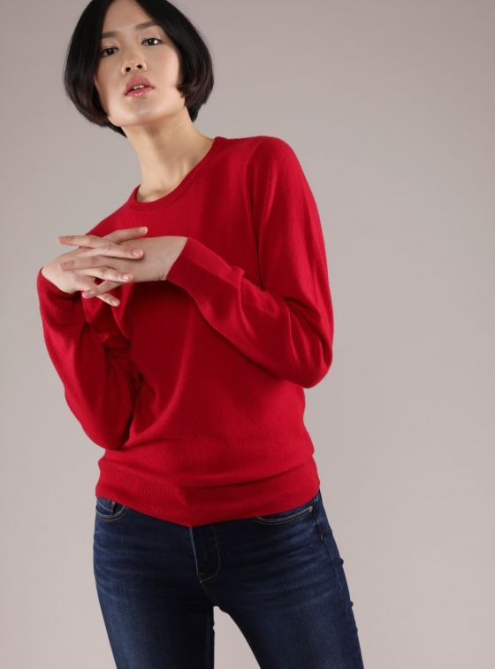 Model wearing a red crewneck cashmere sweater.
