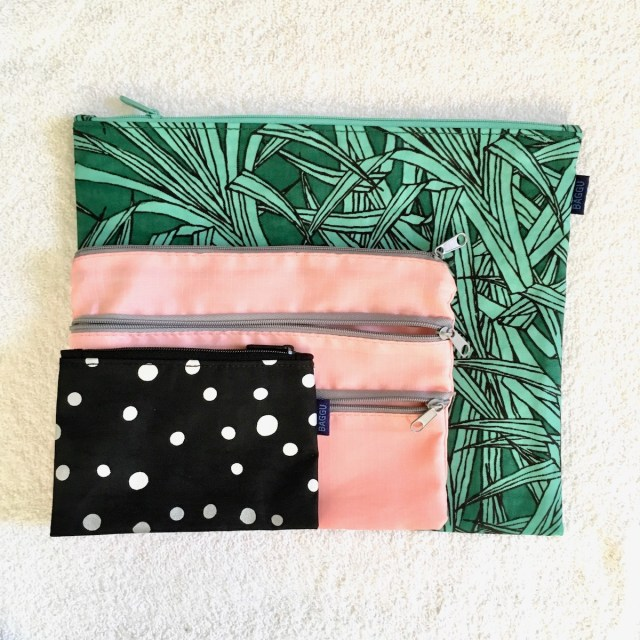 3 zippered pouches stacked on top of each other, largest on the bottom and smallest on top. The large one has a green frond print, the middle one is pink and has 3 zippers, and the small one has white dots on black.