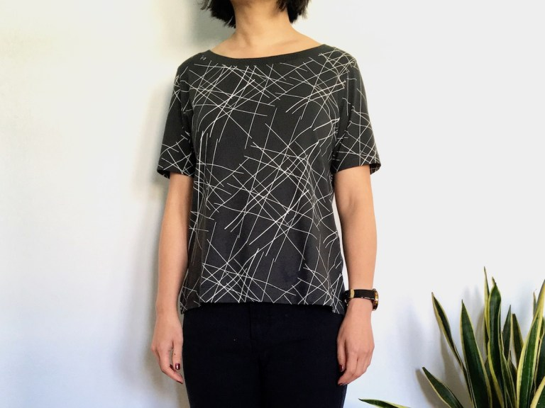 Uniqlo SPRZ Graphic Tee worn by a woman. The T=shirt is gray with white lines.