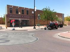 "In that iconic song ""Take it Easy"" recorded by the Eagles there is a line attributed to a hitchhiker who is standing on a corner in Winslow, Arizona who sings ""…when a girl, my lord, in a flat bed Ford slows down to take a look at me…"". A bronze statue stands near a lamp post, securing an acoustic guitar between his right hand and the shoe of his right foot. The red flat bed Ford is just behind the coupe. Too bad about the construction flags. Pretty neat."