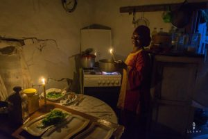 african woman cooking in the kitchen with candle light