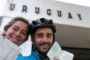 Two cyclists showing passport stamps of Uruguay