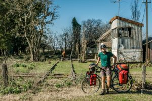 Cyclist standing next to an abandoned railway station