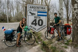 Two cyclists posing in front of 3000 kilometer sign of Ruta 40 in El sosneado