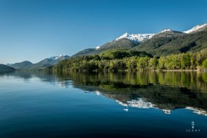 Snow capped mountains reflected on the waters of Lago Lacar