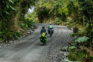 Two cyclists cycling on a dirt on the Carretera Austral