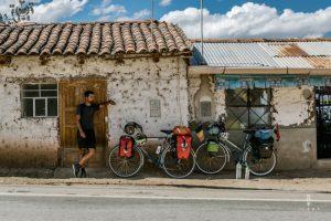 Fietser leunt tegen de muur van lemen huizen in Peru