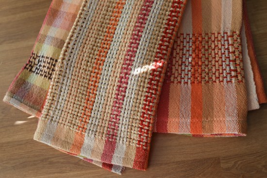 Three tea towels, folded and laying next to one another. Oranges, reds and creams in a lace pattern.