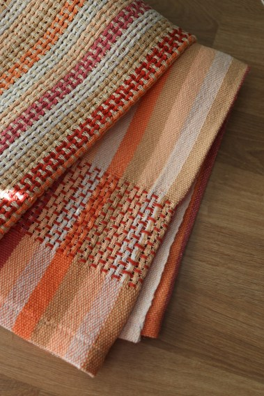 Tea towel folded and laying on a table with a red woven lace panel and striping for the warp.