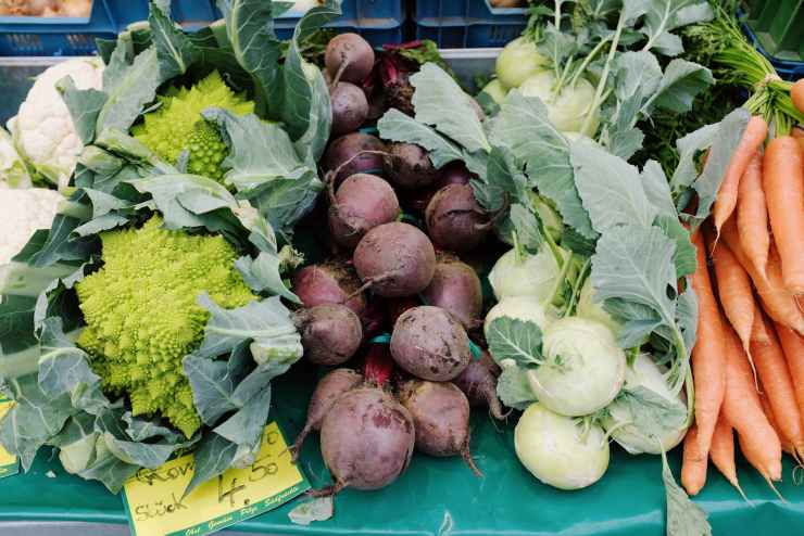 assorted fresh ripe vegetables in market stall