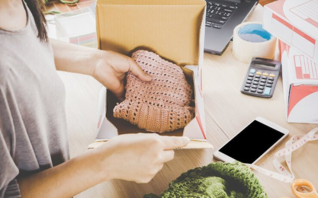 Woman packing clothes into shipping box that she sold online
