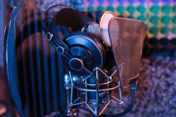 Headphones on top of a recording mic set up with pop filter