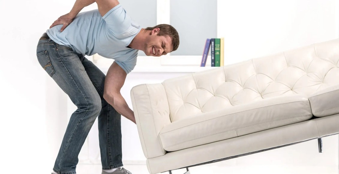 man trying to lift couch wrong way ends up with back pain
